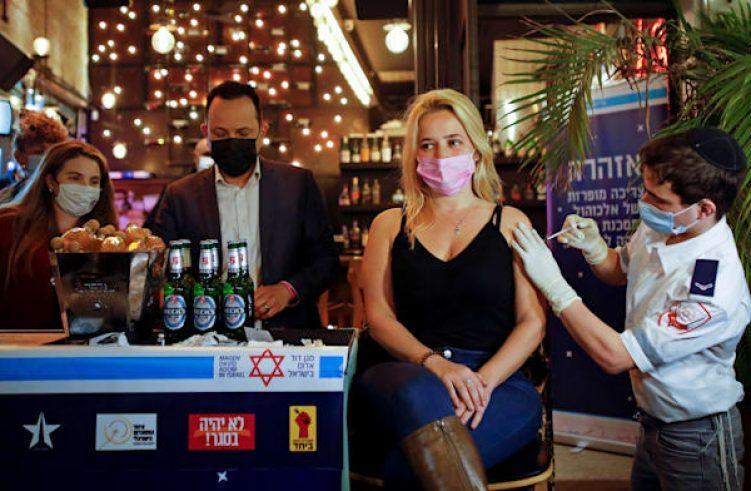 אשה מקבלת חיסון בפאב בתל אביב